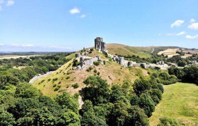 corfe-castle-sat-on-top-of-green-hill-in-summer-castles-in-dorset