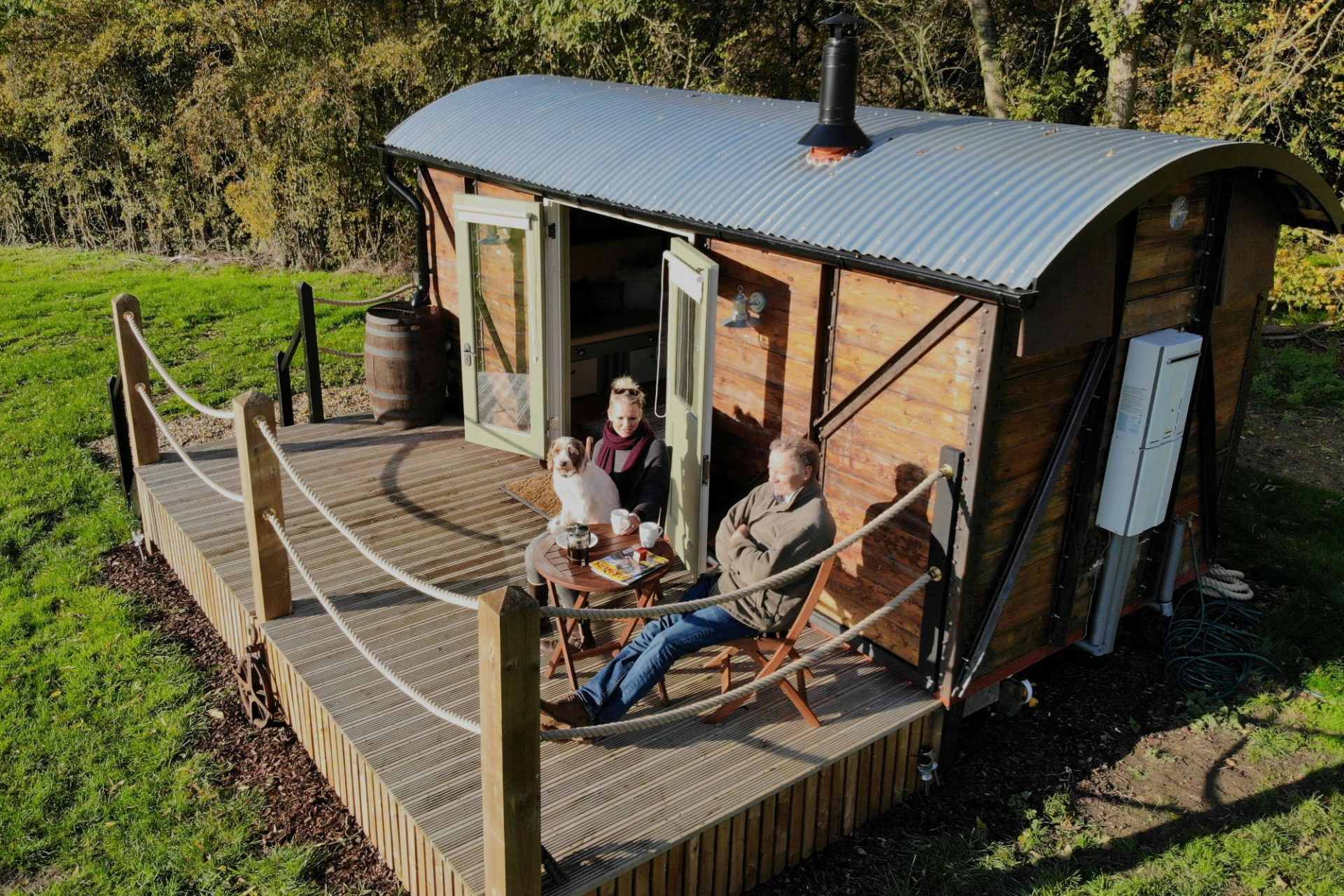 couple-and-dog-sat-on-decking-outside-choo-choo-moo-victoria-victorian-carriage