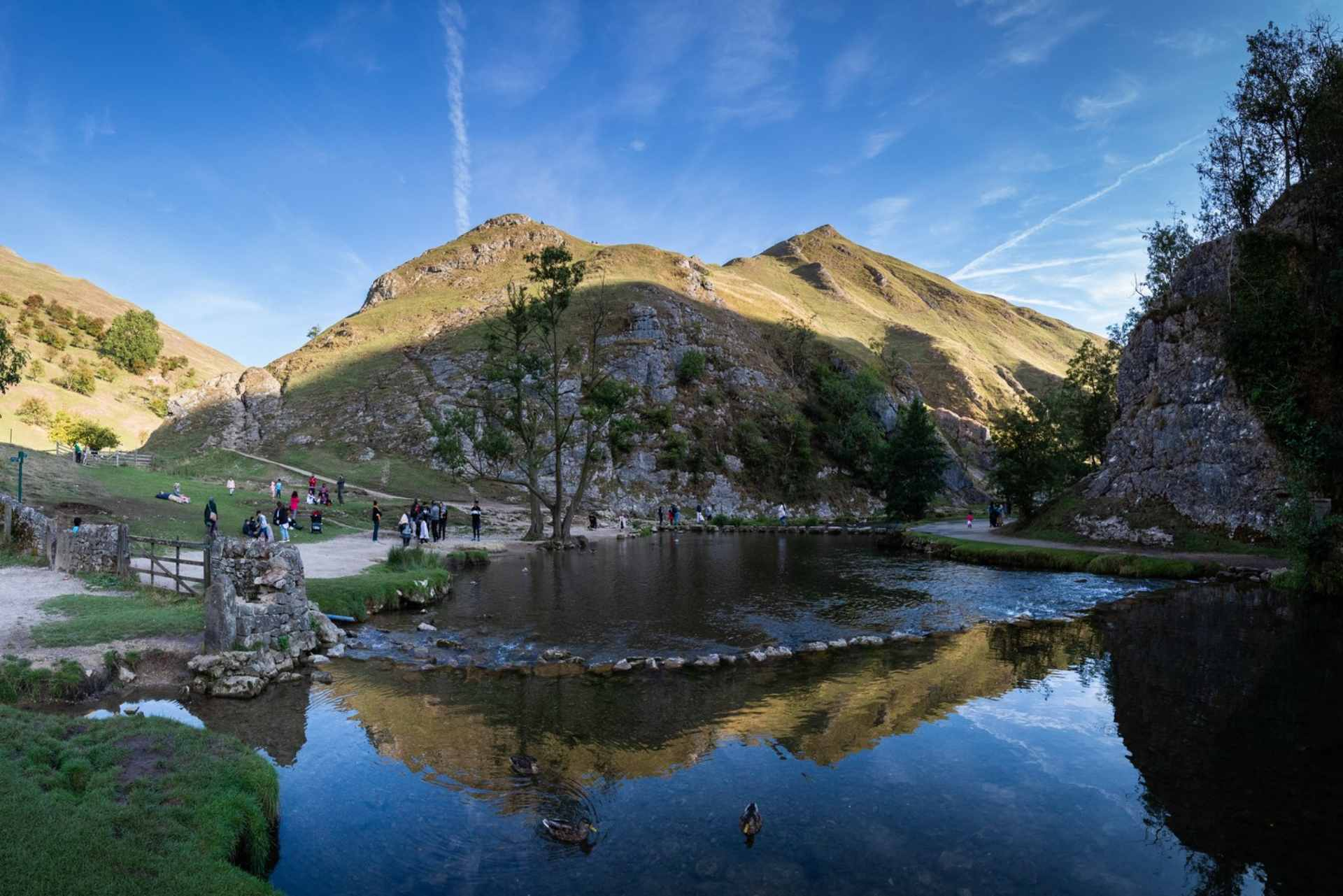 dovedale-stepping-stones-crossing-river-in-front-of-hill-on-sunny-day-best-peak-district-walks