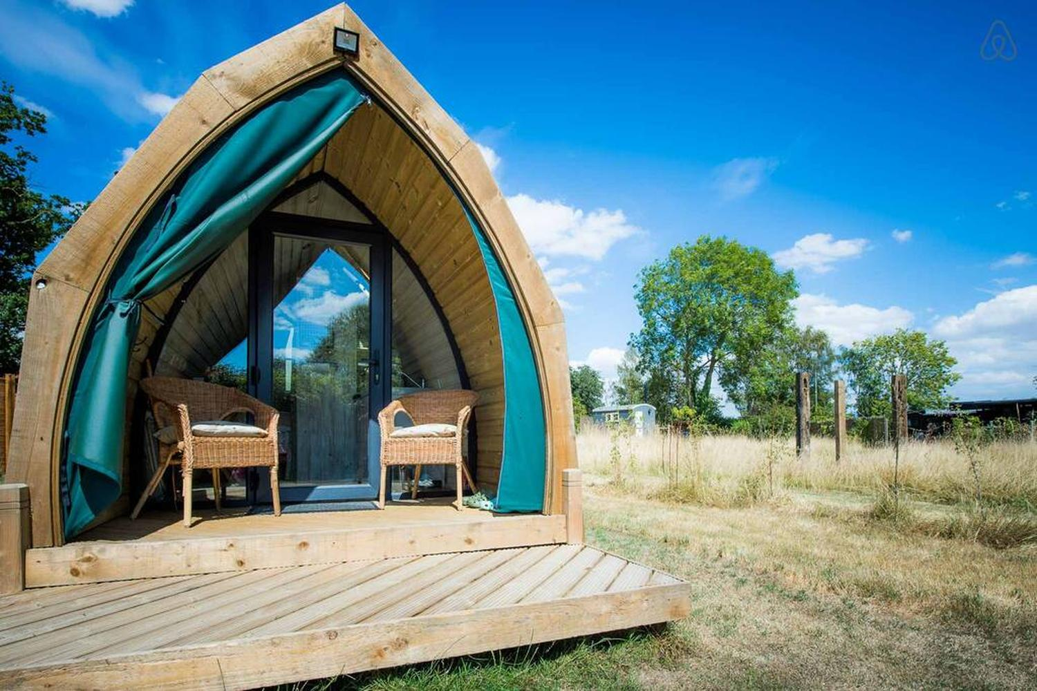 freddie-glamping-pod-on-decking-with-chairs-in-field-on-sunny-day
