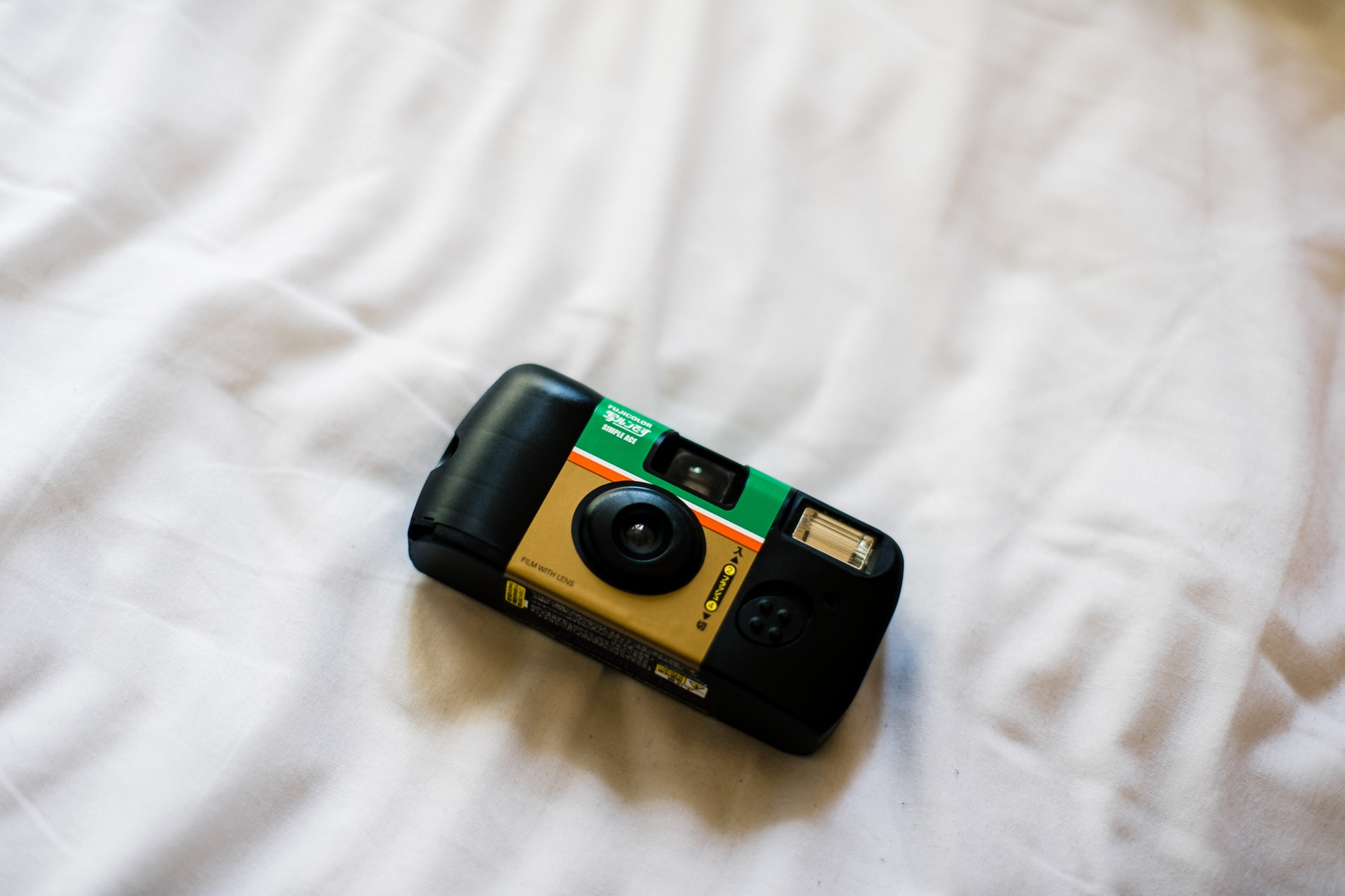 fujicolor-disposable-camera-on-white-bed-sheets