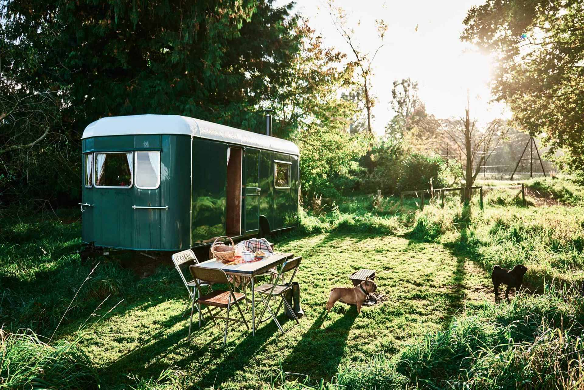 green-gertie-wagon-with-outdoor-seating-area-in-field-at-sunset-at-mad-dogs-and-vintage-vans-glamping-herefordshire