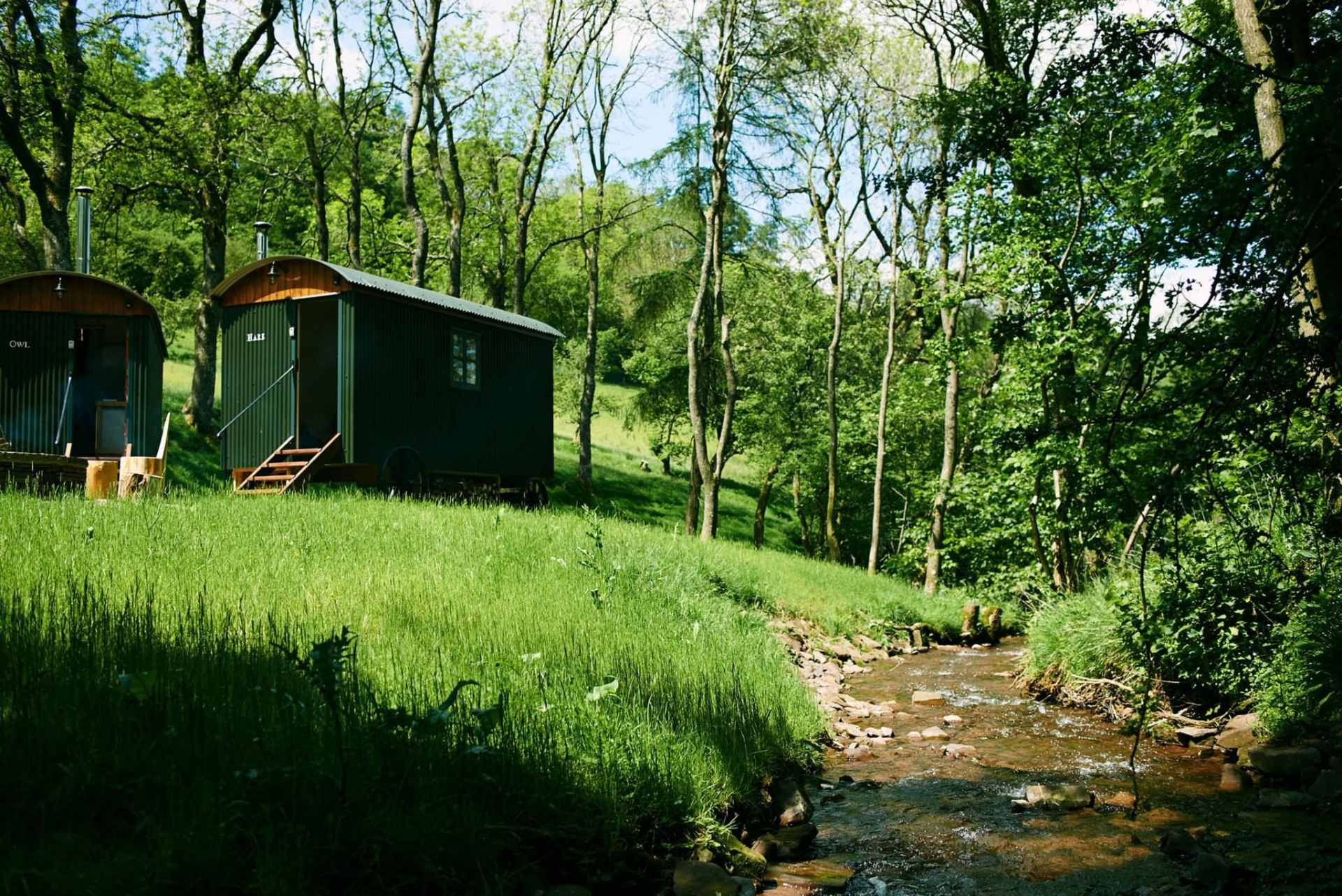 green-shepherds-huts-on-river-bank-in-forest-by-river-huts-in-the-hills