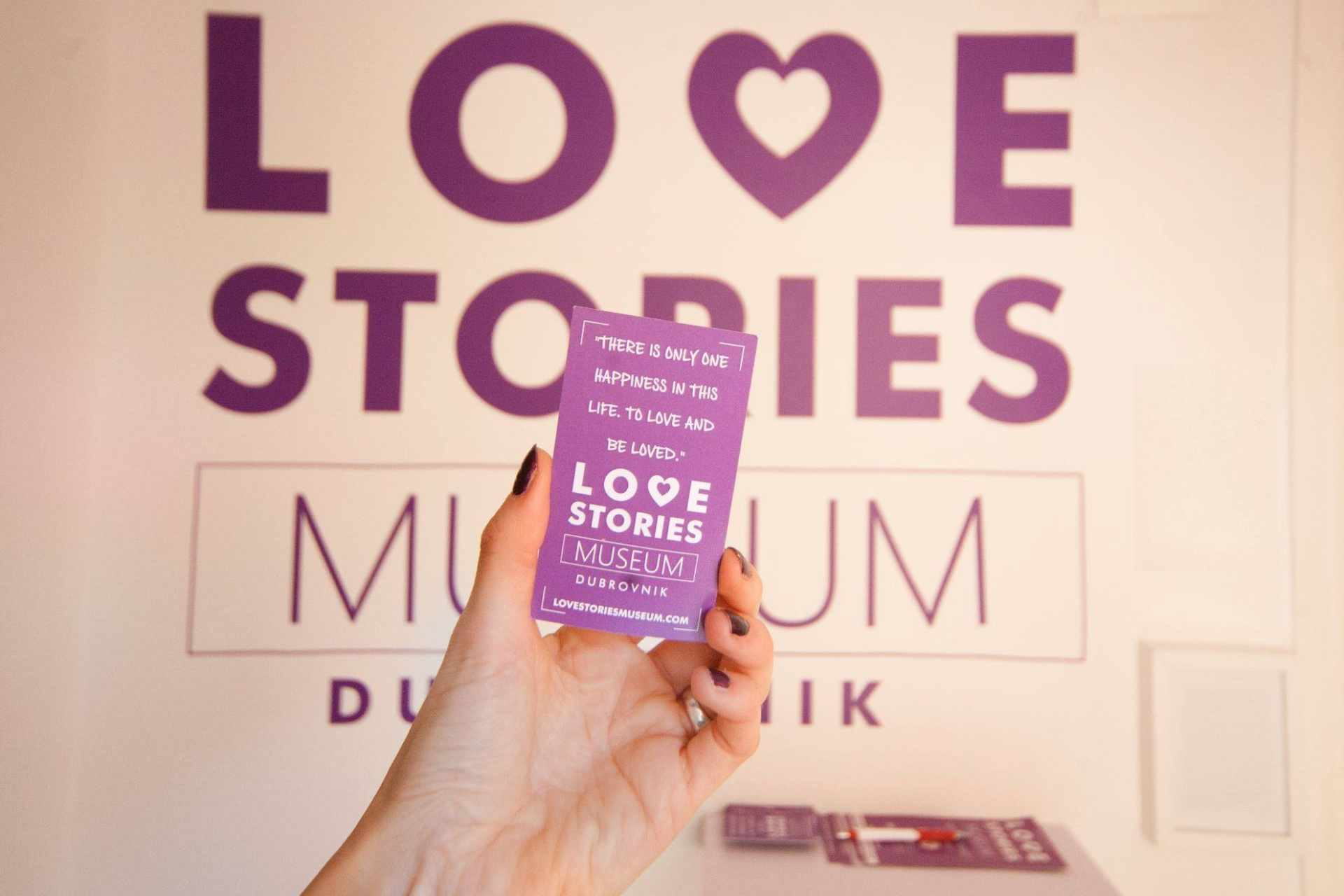 hand-holding-purple-ticket-to-love-stories-museum-in-front-of-museum-sign