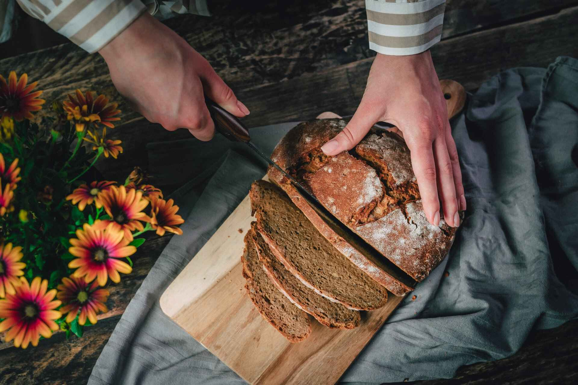 hands-slicing-into-a-loaf-of-brown-bread-on-cutting-board