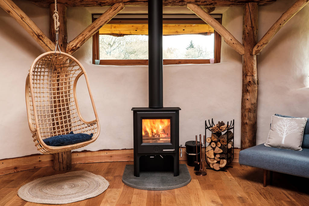 hanging-seat-woodburner-and-sofa-in-cosy-living-area-of-willow-roundhouse-round-the-woods