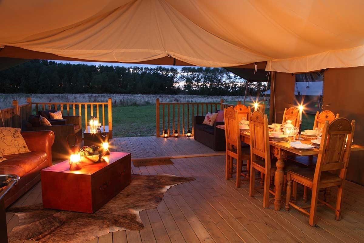inside-living-area-with-table-and-sofas-of-wild-luxury-safari-tents-at-night