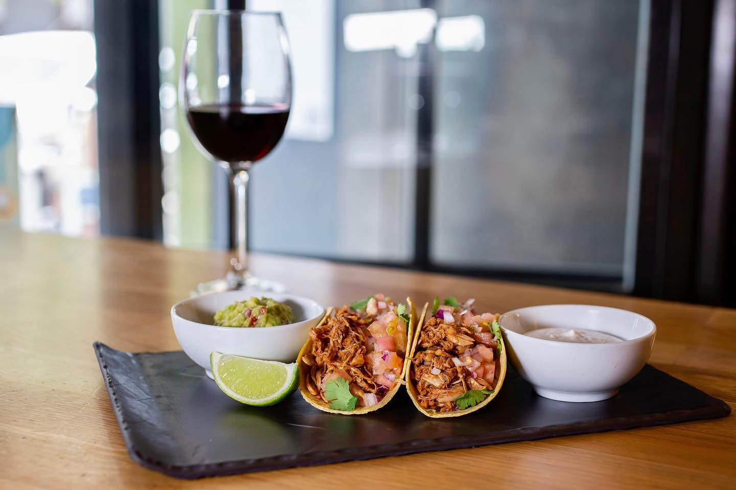 jackfruit-tacos-on-black-slate-on-restaurant-table-with-glass-of-red-wine-restaurante-copenhagen