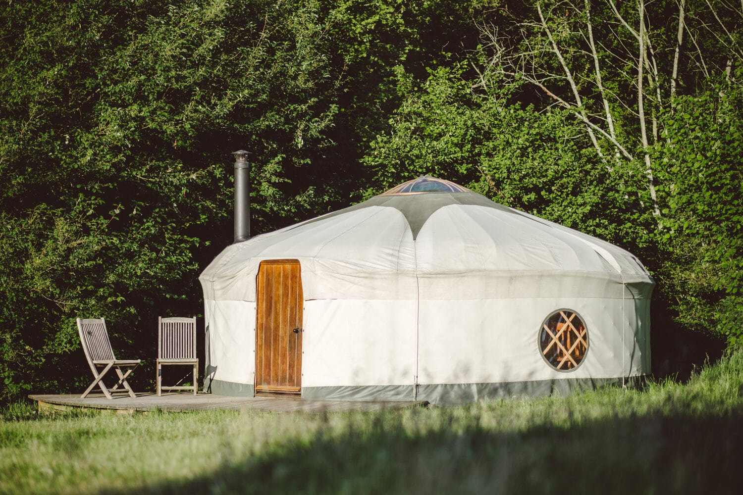 large-white-yurt-on-decking-with-deck-chairs-in-green-field-on-sunny-day-round-the-woods