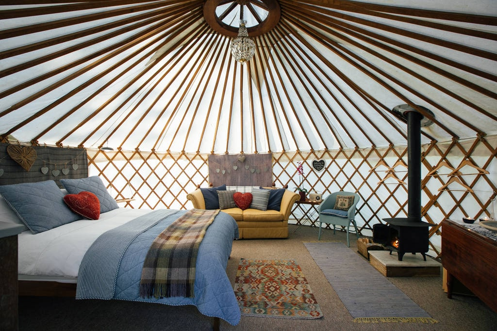 living-area-with-large-double-bed-sofa-and-woodburner-in-burlingham-yurt