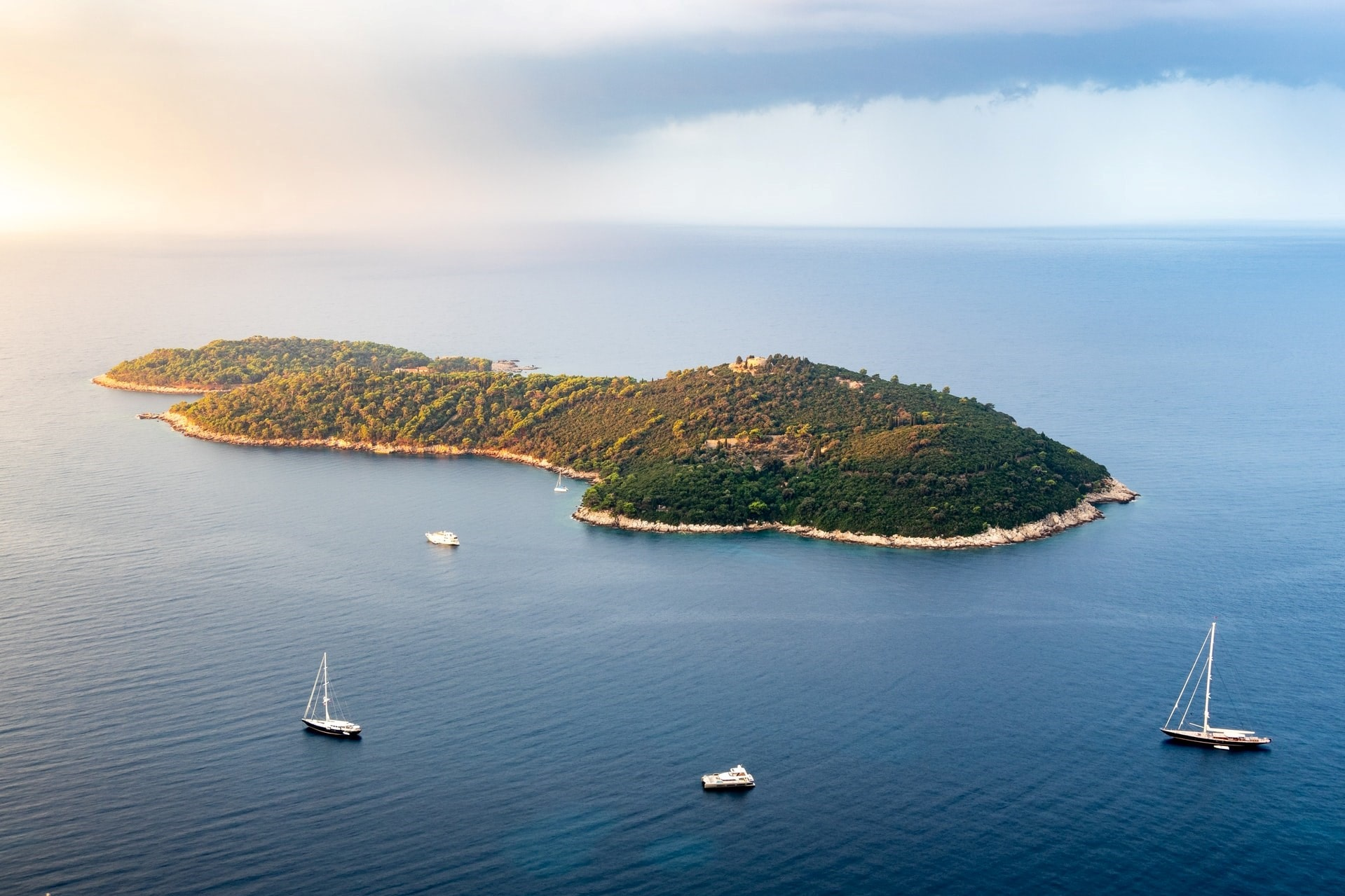 lokrum-island-in-blue-sea-surrounded-by-white-sailboats-at-sunset-3-days-in-dubrovnik-itinerary