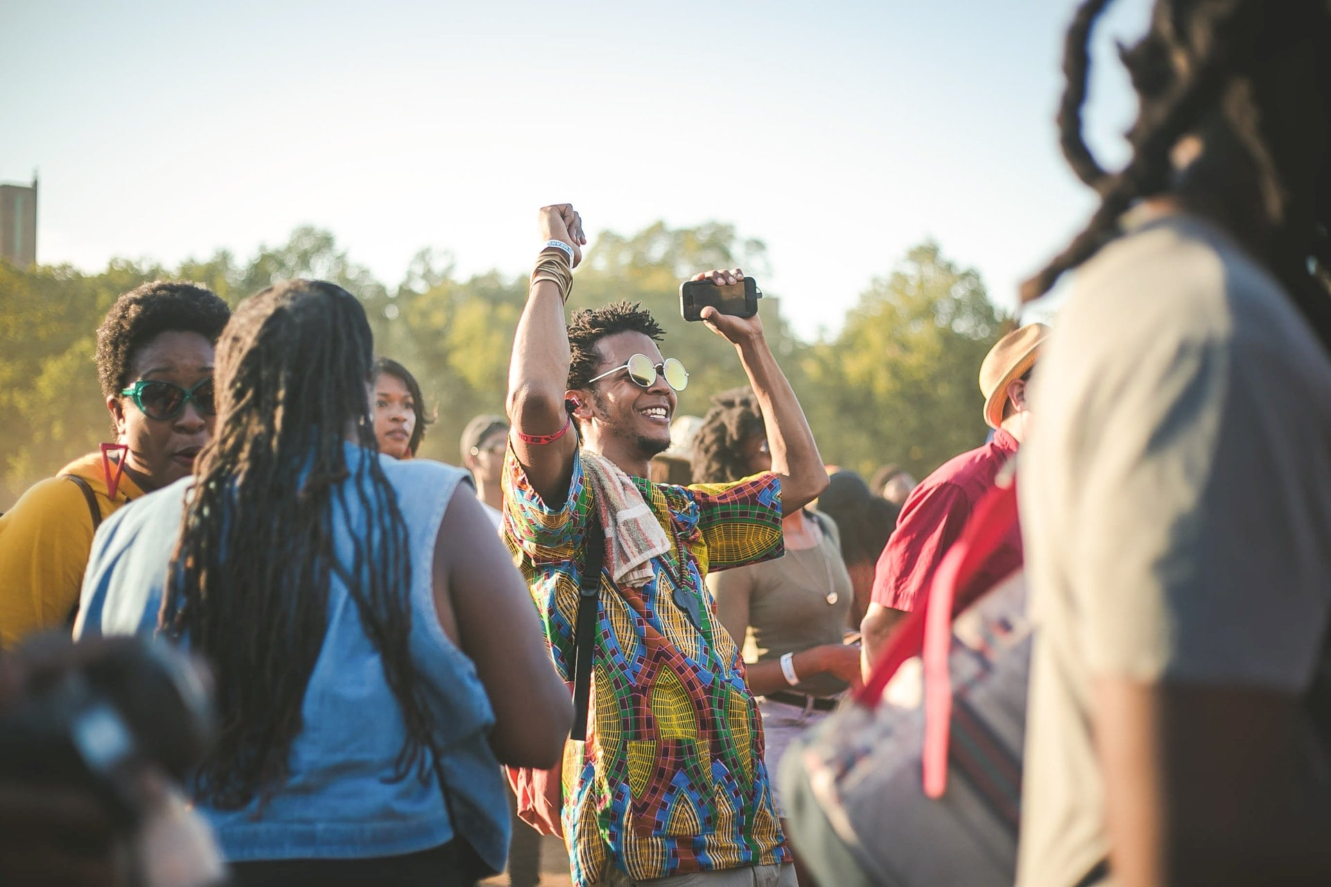 man-in-vibrant-shirt-and-sunglasses-dancing-in-festival-crowd-in-daytime-packing-list-for-festival