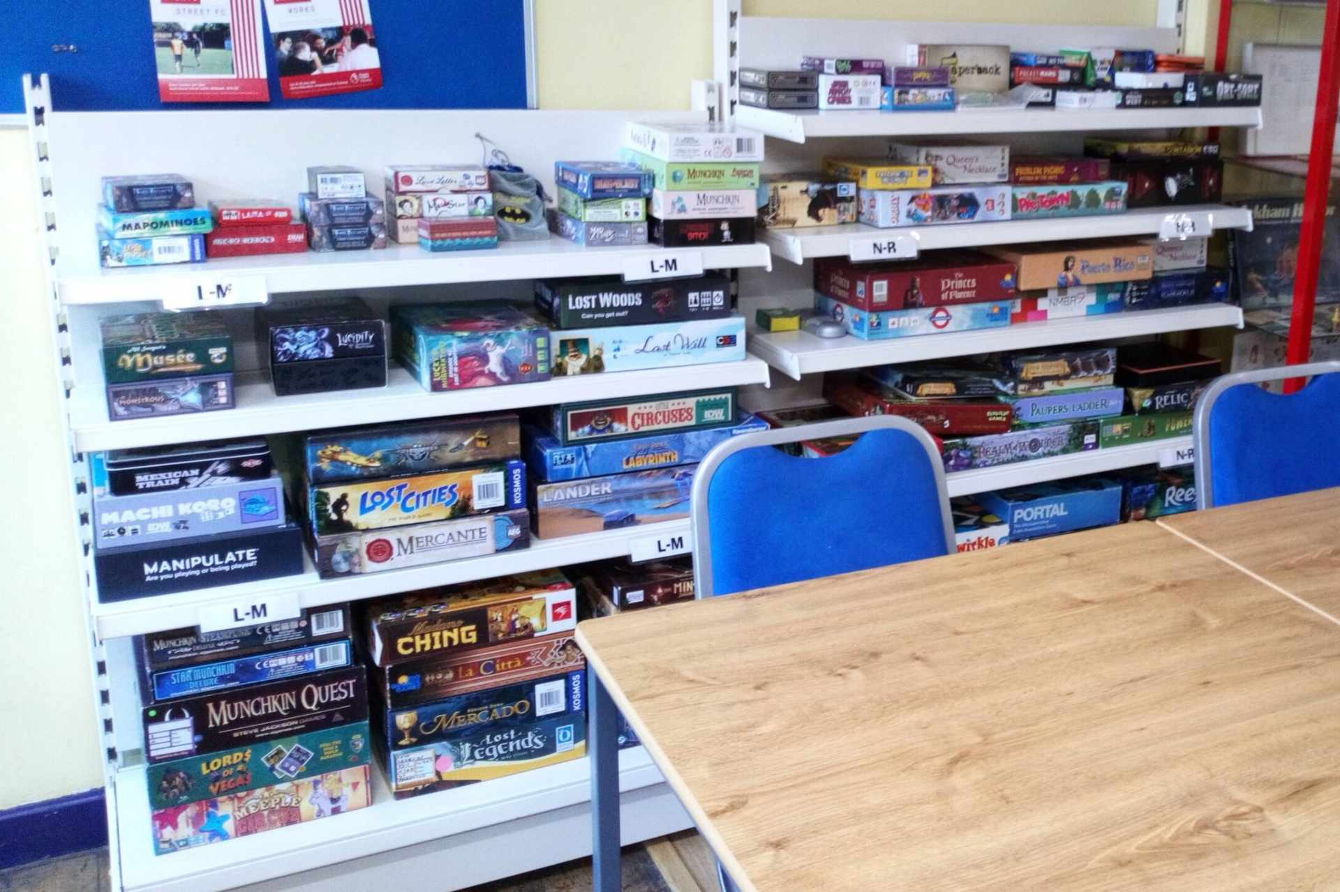 piles-of-board-games-on-shelves-by-table-and-chairs-board-in-the-city