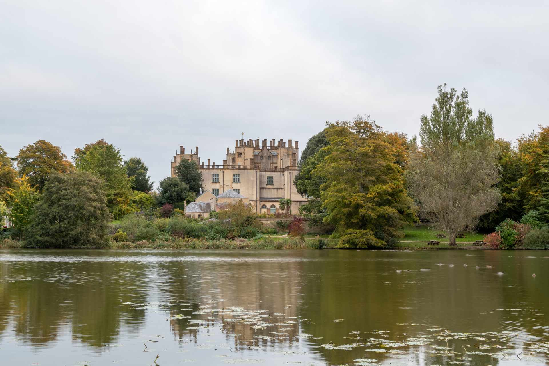 sherborne-castle-across-lake-on-cloudy-day-with-autumn-trees-on-grounds