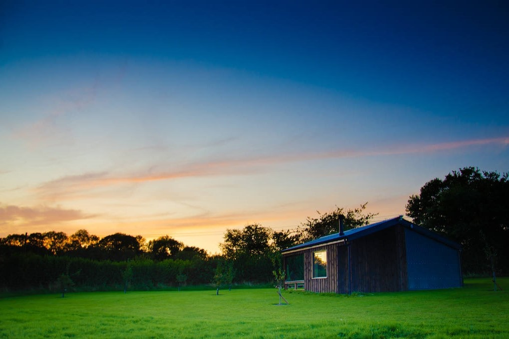 small-pax-cabin-at-the-arbour-in-green-field-at-sunset