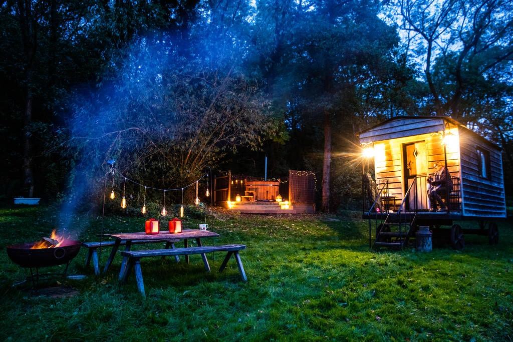 tawny-owl-shepherds-hut-hot-tub-picnic-table-and-bbq-lit-up-at-night