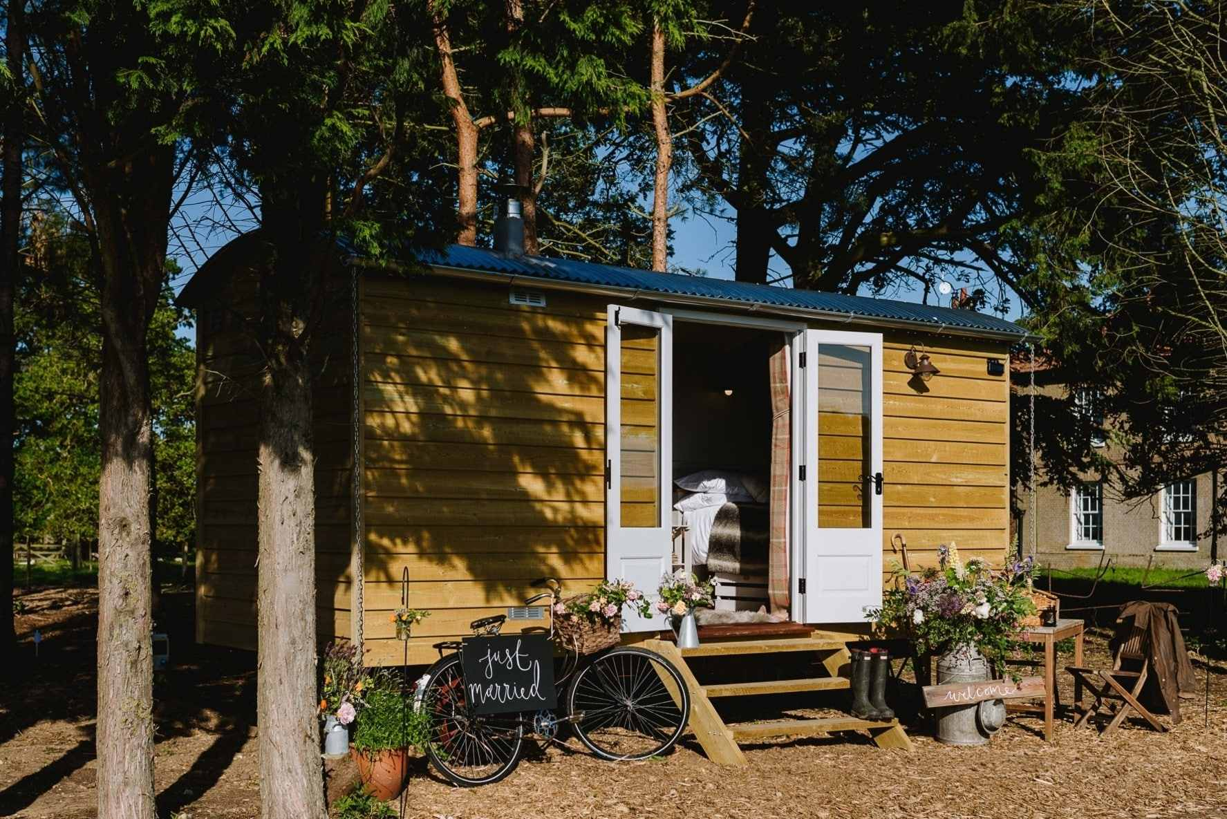 the-herdwick-hideaway-godwick-shepherds-hut-amid-trees-with-bike-at-front