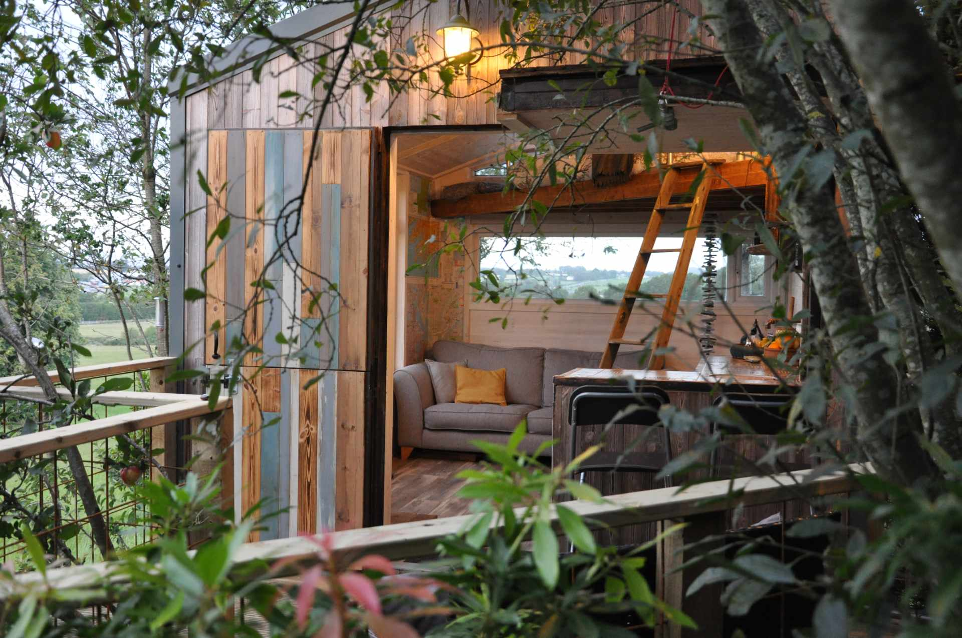 the-hideout-treehouse-living-area-seen-through-trees-in-wexford-treehouses-ireland