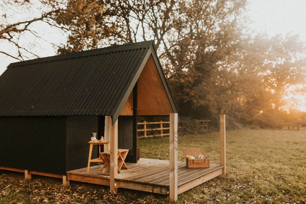 triangle-litte-hut-in-field-at-sunset-at-the-fire-pit-camp