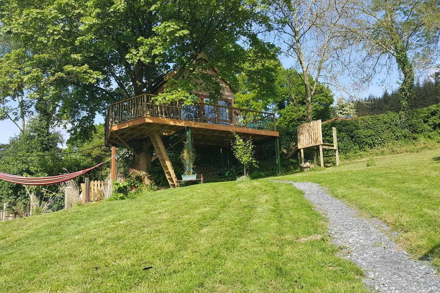 tuckmill-treehouse-with-hammock-at-top-of-green-field