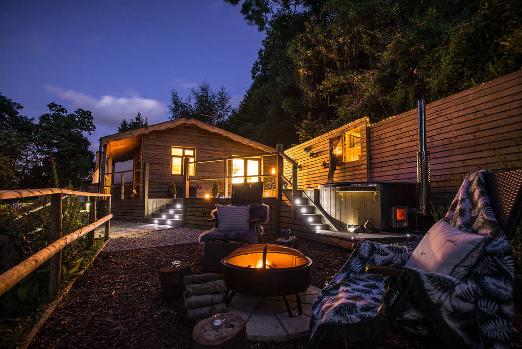 watsons-cabin-with-outdoor-hot-tub-and-fire-pit-lit-up-at-night-glamping-herefordshire