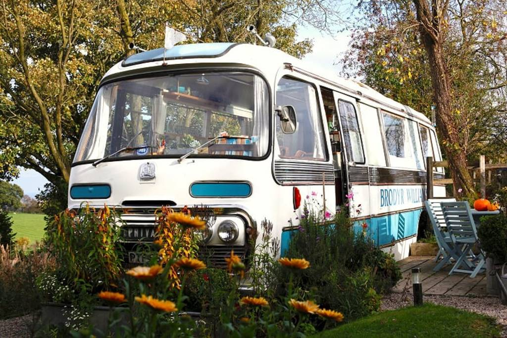 white-and-blue-majestic-bus-with-outdoor-decking-in-field