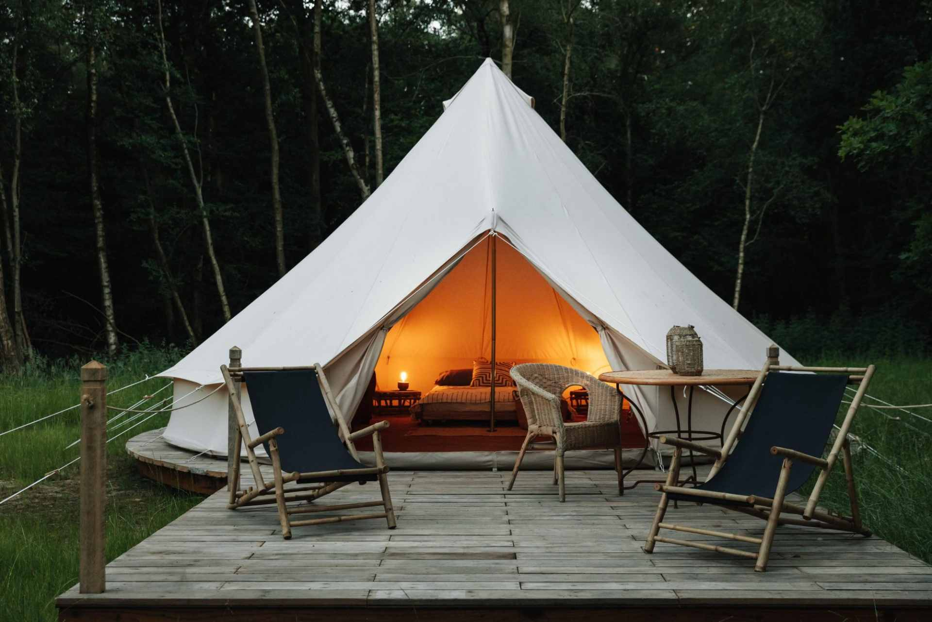 white-bell-tent-on-deck-with-chairs-lit-up-in-evening-settle-canvas-camp