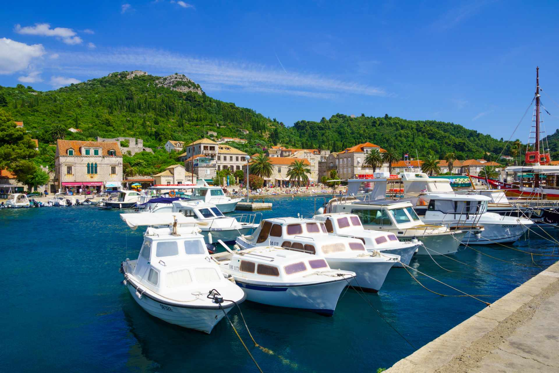 white-boats-on-blue-sea-at-lopud-harbour-with-hills-in-background-3-days-in-dubrovnik-itinerary