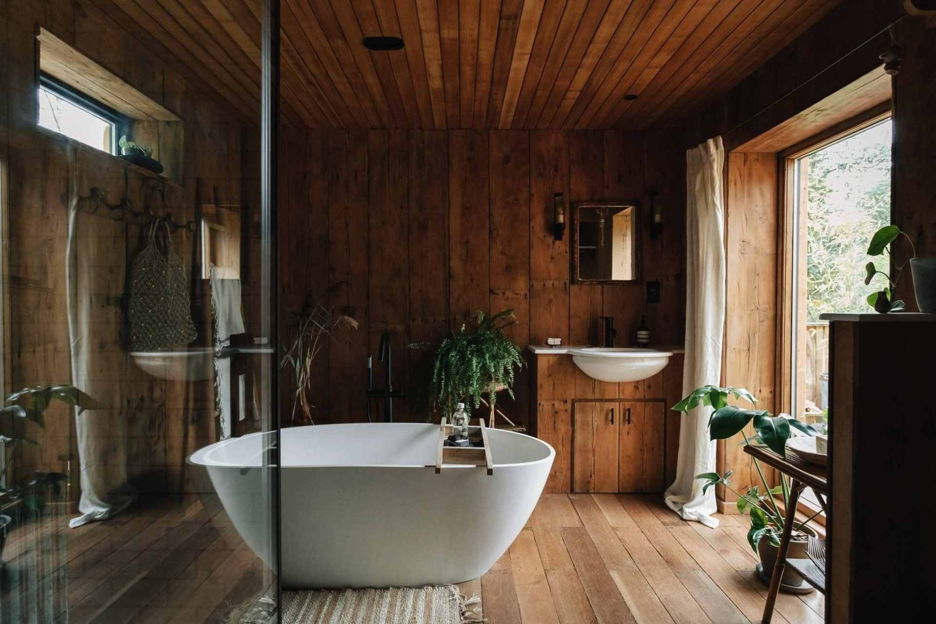 white-freestanding-bath-in-wooden-cabin-with-lots-of-green-plants-settle-cabin-norfolk-glamping