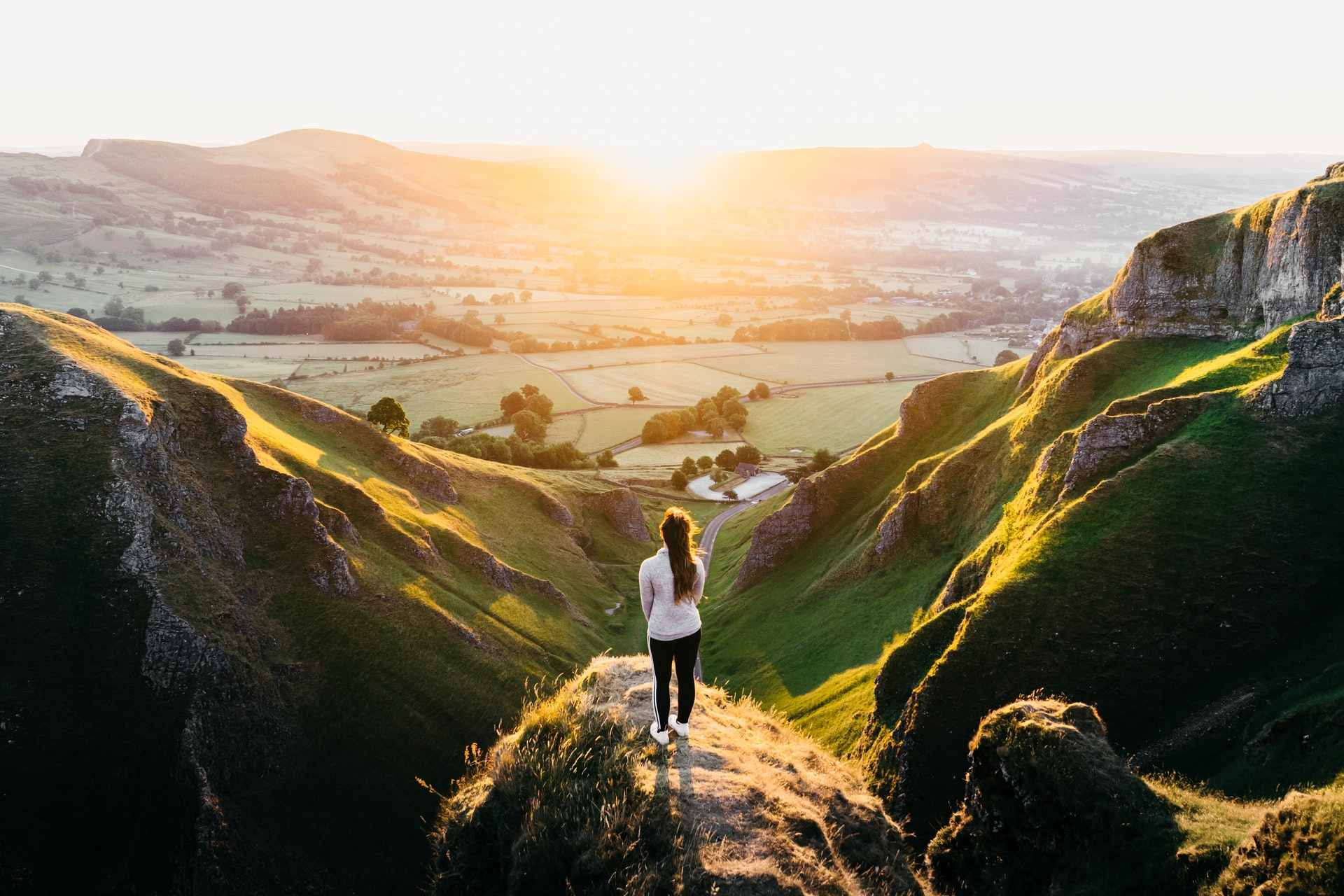 woman-standing-on-rock-overlooking-winnats-pass-winding-road-and-countryside-at-sunset-best-peak-district-walks