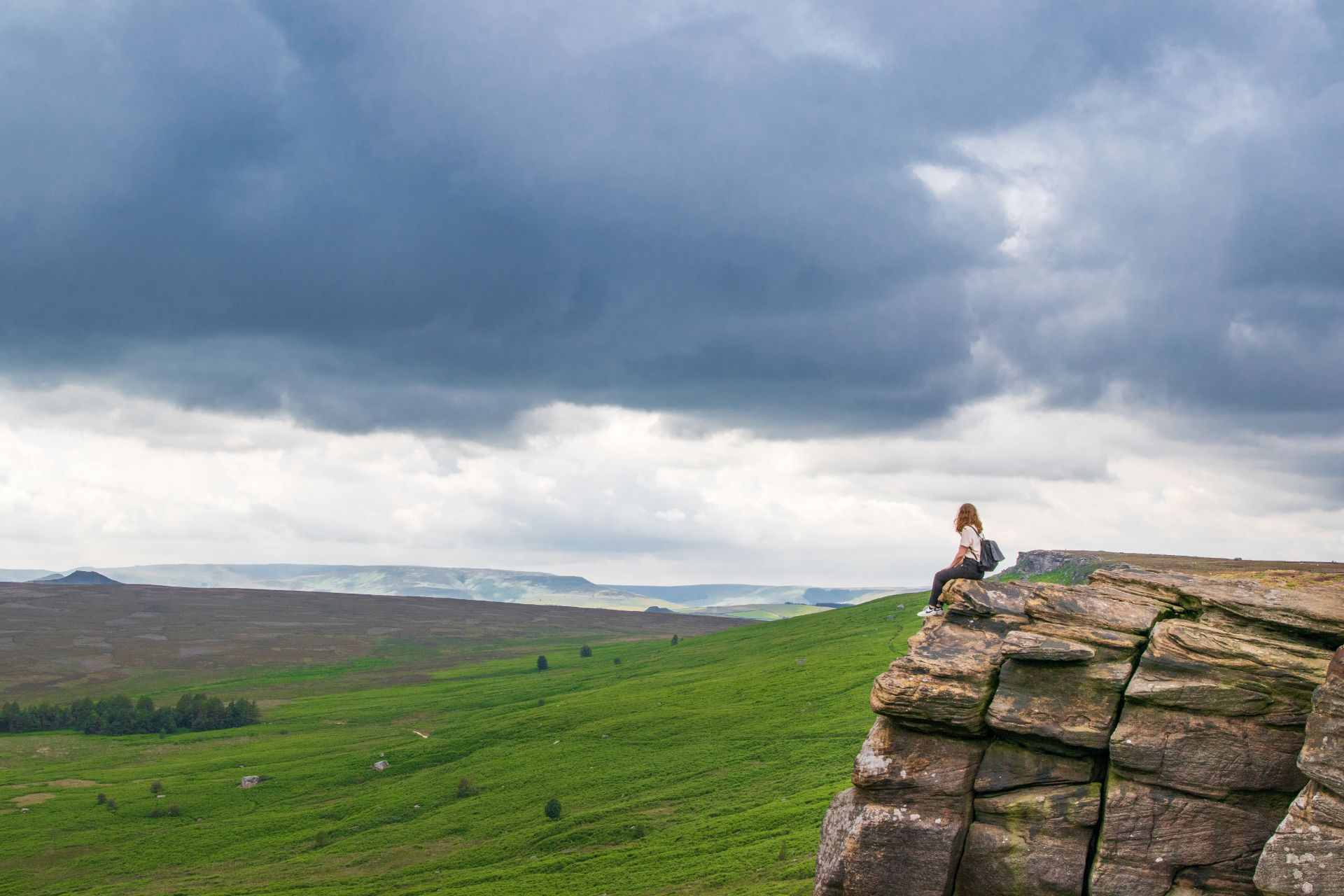 woman-wearing-backpack-sat-on-rock-cliff-face-overlooking-green-fields-and-hills-on-a-moody-cloudy-day-at-stanage-edge